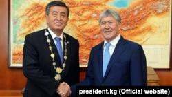 Қырғызстан президенті Сооронбай Жээнбеков (сол жақта) өзін ұлықтау салтанатында экс-президент Алмазбек Атамбаевтың қолын алып тұр. Бішкек, 24 қараша 2017 жыл.