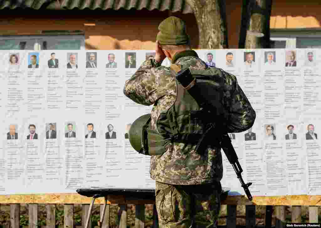 A Ukrainian serviceman studies presidential candidates at a polling station near the front line against Russia-backed separatists, in the village of Zaitseve, eastern Ukraine. (Reuters/Gleb Garanich)
