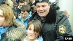 Екатерина Самуцевич, участница панк-группы Pussy Riot, покидает здание суда с полицейским. Москва, 10 октября 2012 года.