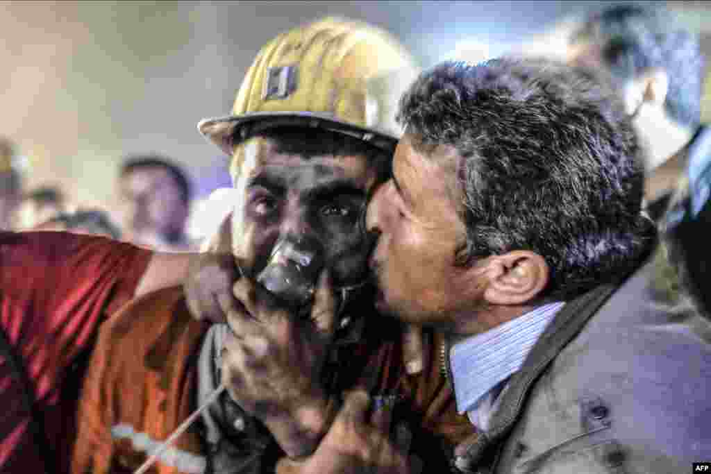 A man kisses his son, who survived an explosion in a coal mine in Manisa, Turkey, which killed hundreds of people on May 13. (AFP/Bulent Kilic)