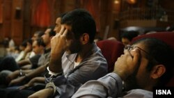 Iranian opposition suspects cover their faces during their second hearing at a revolutionary court in Tehran on August 8.