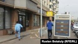 Прохожие рядом с пунктом обмена валют в Астане.
