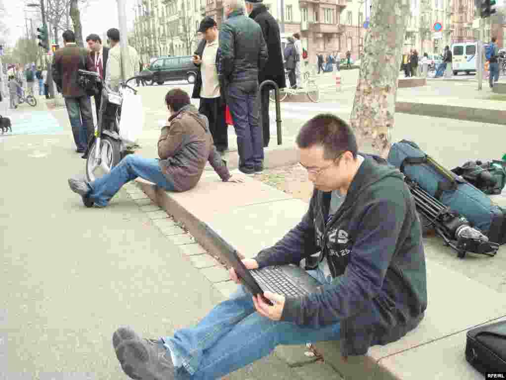 Страсбург орталығында кептелісте тұрып қалған қытайлық журналист сол жерден -ақ хабар беруде. 3 сәуір 2009 жыл. - Журналист из Китая, застрявший на улице Страсбурга во время освещения саммита НАТО. 3 апреля 2009 года.