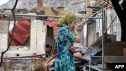 An ethnic Uzbek woman cries as she passes by a burnt-out house in Osh on June 24, 2010.
