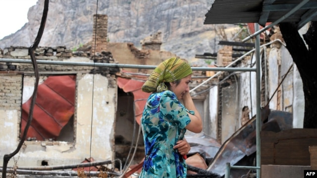An ethnic Uzbek woman cries as she passes by a burned-out house in Osh on June 24.