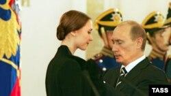 Президент России Владимир Путин (справа) вручает премию Светлане Захаровой.