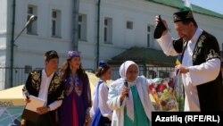 Татар бистәсенең иң өлкән вәкиле Нурания апа алып килгән бүләкләрне күрсәтә