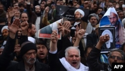 Afghan Shi'a hold posters and chant slogans during a demonstration in Herat on January 3.
