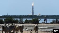 Прохожие наблюдают за запуском ракеты на индийском космодроме. 22 июня 2016 года.
