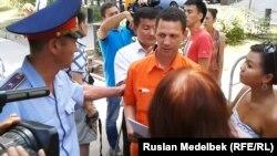 Полицейский говорит с участниками акции у здания консульства Франции в Алматы. 1 августа 2013 года.