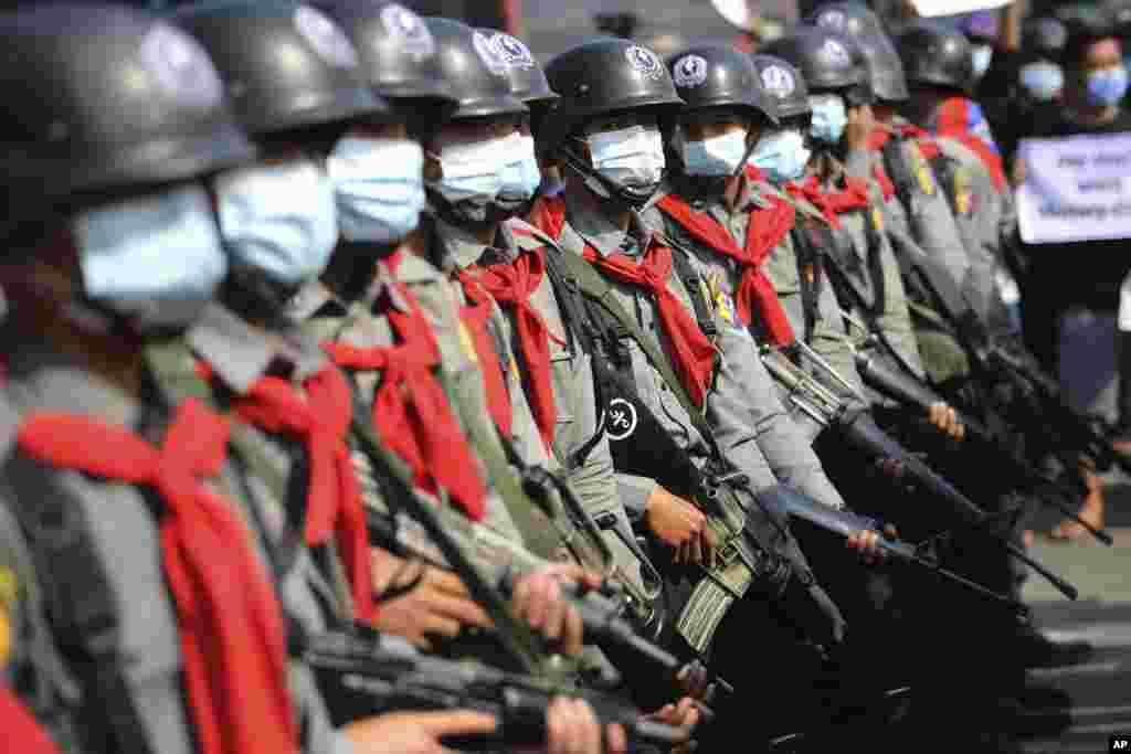 Policë të veshur me rroba për kontrollimin e trazirave shihen pranë protestuesve në Naypyitaw, Mianmar, 8 shkurt 2021. (AP)