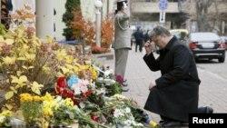 Президент Украины Петр Порошенко выражает соболезнование народу Франции в связи с терактами, преклонив колени у посольства Франции. Киев, 14 ноября 2015 года.