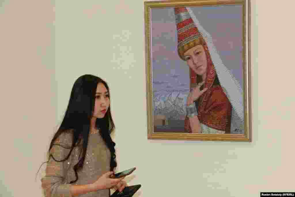 Рядом с картиной, где изображена девушка в казахской национальной праздничной одежде.