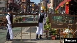 Официанты нью-йоркского ресторана перескивают прозрачные щиты, которые устанавливают для соблюдения дистанции между посетителями на летней площадке. 25 июня 2020 года.