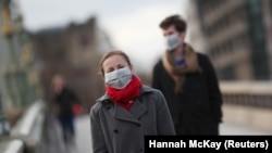 Люди в захисних масках на вулицях Лондона