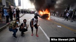 An Atlanta Police Department vehicle burns as people pose for a photo during a demonstration against police violence on May 29.