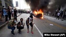 Policijsko vozilo u plamenu dok ljudi poziraju za fotografiju tokom demonstracija protiv policijskog nasilja u Atlanti 29. maja.