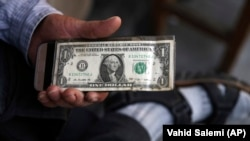 An Iranian street money changer holds a U.S. banknote in downtown Tehran, July 30, 2018
