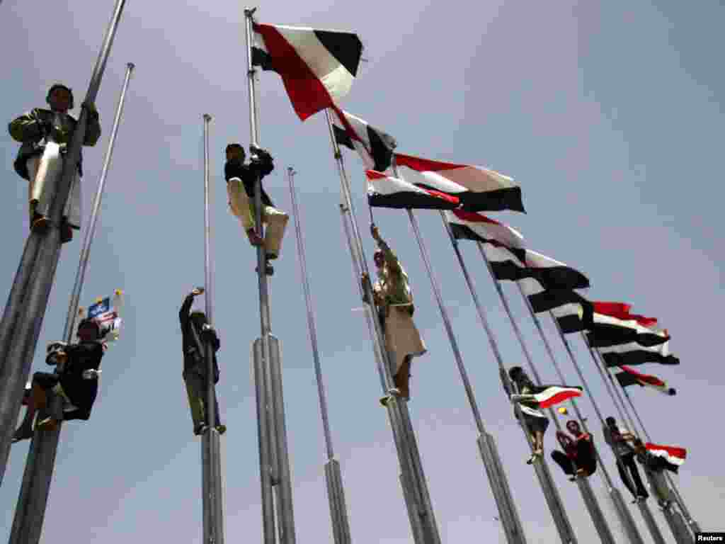Supporters of Yemen's President Ali Abdullah Saleh climb flag poles during a rally in Sanaa on May 13.Photo by Khaled Abdullah for Reuters