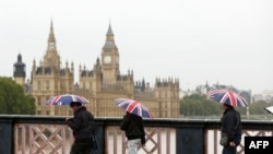 Люди на мосту рядом со зданием парламента в Лондоне. Лондон, 23 сентября 2012 года.