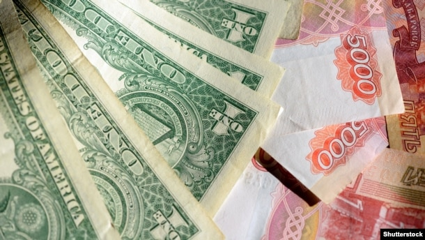 Российский рубль подешевел наполовину в сравнении с долларом в результате санкций и падения цен нефти