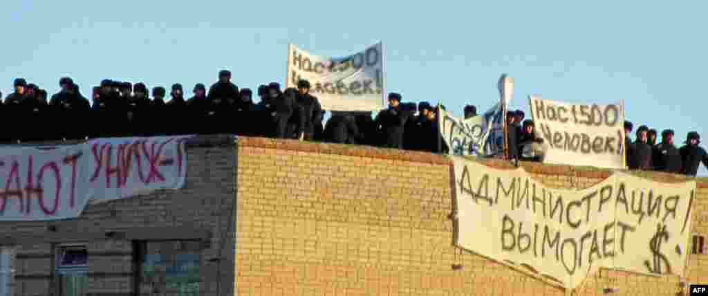 "A group of inmates stands on a rooftop inside the prison. Two of the signs read, ""We are 1,500 human beings!"""