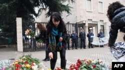 People put flowers in front of the building where three people were killed in an anti-government protest.
