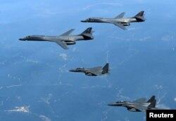 Американские бомбардировщики B-1B в сопровождении истребителей в небе над 38-й параллелью над Корейским полуостровом
