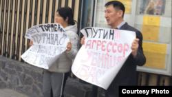 Гражданский активист Нурлан Карымшаков с женой Гульзаной Имаевой пикетируют у посольства России в Кыргызстане. Бишкек, 27 марта 2019 года.