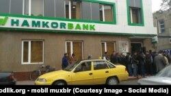 Узбекистанцы стоят в очереди у двери «Хамкорбанка», чтобы получить денежные переводы через систему Western Union.