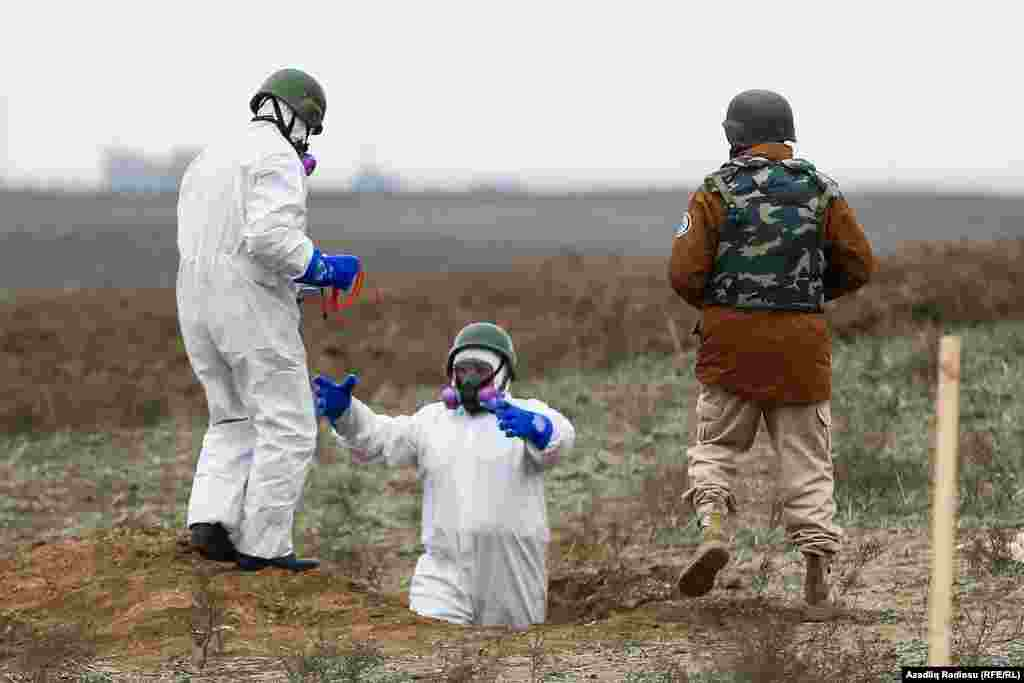 Azerbaijani mine-clearance officers prepare to detonate unexploded munitions.