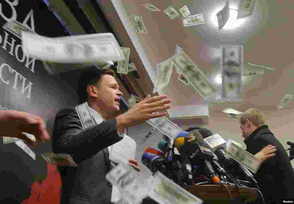 An unidentified person throws pieces of paper, resembling banknotes, as Russian opposition figure Ilya Yashin (left) presents his report, titled National Security Threat and dedicated to the current situation in Chechnya and its leader, Ramzan Kadyrov, on February 23. (Reuters/Maksim Shemetov)