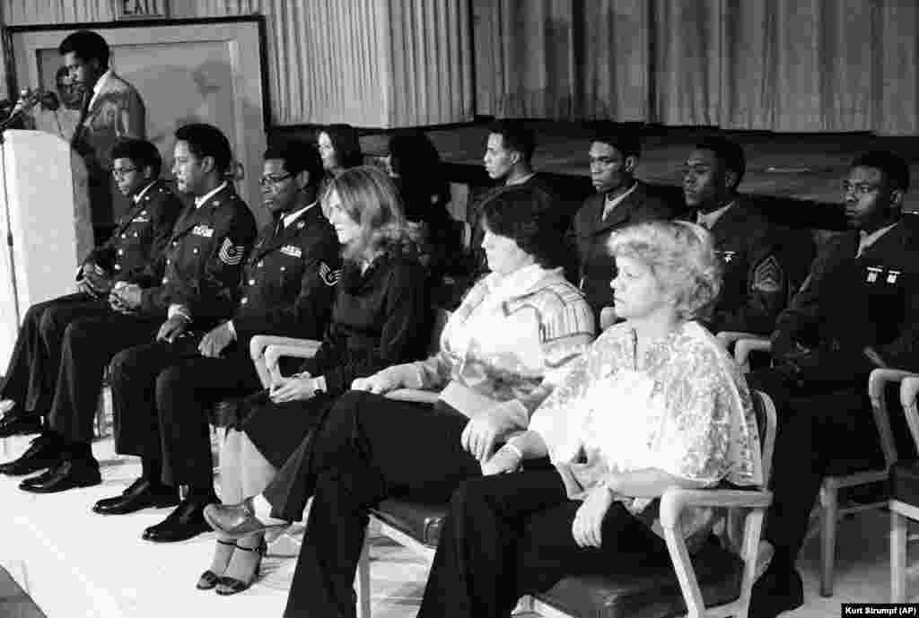 Thirteen Americans were freed on November 21, 1979, and taken to the U.S. Air Force base in Wiesbaden, West Germany, where they appeared before journalists. Lloyd Rollins, at the podium, read a statement from their former captors. Front row from the left: Terry Robinson, Joseph Vincent, James Hughes, Joan Walsh, Kathy Gross, and Anne Johnson. Back row from left: Terry Tedford, Liz Montagne, Wesely Williams, William Quarles, Ladell Maples, and David Walker.