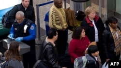 An official checks passengers' identification prior to entering a security checkpoint at Ronald Reagan Washington National Airport in Arlington, Virginia.