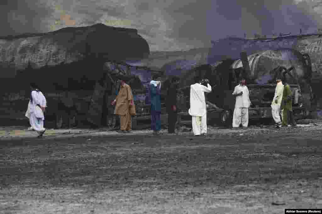 Local residents gather near tankers of a NATO supply convoy after an attack a day earlier in Hub, Pakistan. (Reuters/Akhtar Soomro)