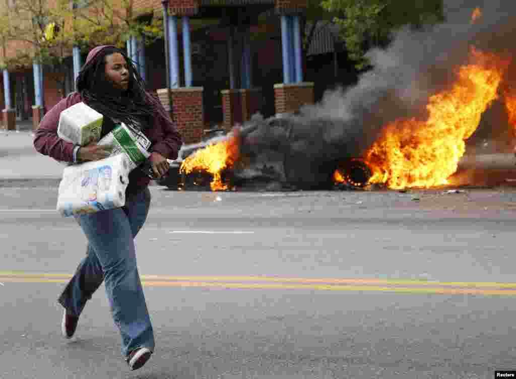 Женщина с товарами из разграбленного во время беспорядков магазина в Балтиморе