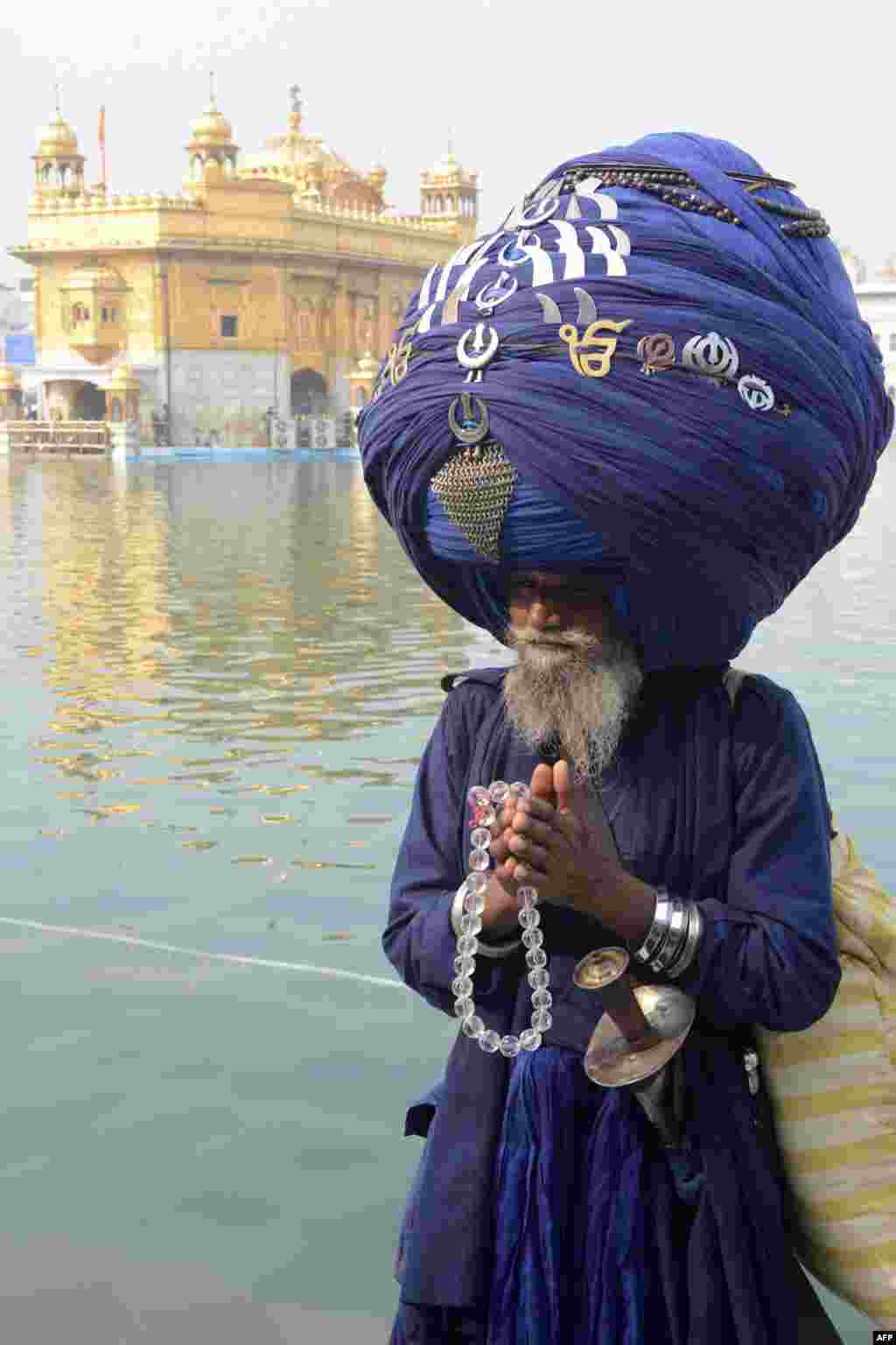 An Indian member of the Sikh Nihang Army wears a turban of more than 300 meters in length at the Maghi Mela festival at the Sikh Shrine Golden Temple in Amritsar, India. Maghi Mela follows the Lohri or harvest festival and commemorates fighters in the Battle of Khidrana fought between the Mughal Army and the 10th Sikh Guru, Gobind Singh Ji. (AFP/Narinder Nanu)