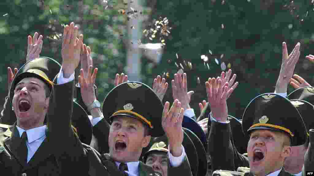 Belarusian cadets throw coins in the air during a graduation ceremony at the Military Academy outside Minsk on July 1. (AFP/Viktor Drachev)