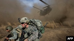 FILE U.S. and Afghan soldiers race to get out of the way of a CH-47 Chinook helicopter landing.