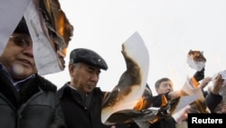 Opposition leaders in Almaty burn election lists during a protest against the results of Kazakhstan's parliamentary elections.