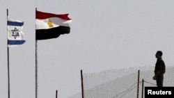 Egypt -- A soldier stands near the Egyptian national flag and the Israeli flag at the Taba crossing, 26Oct2011