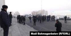 Полицейский наблюдает за участниками акции протеста против девальвации тенге. Алматы, 12 февраля 2014 года.