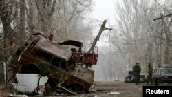 Pro-Russian separatists stand guard next to cars damaged during fighting between the rebels and Ukrainian government forces near Donetsk's airport on December 16.