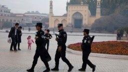 Патруль службы безопасности на фоне мечети в Кашгаре, городе в Синьцзяне. 4 ноября 2017 года.