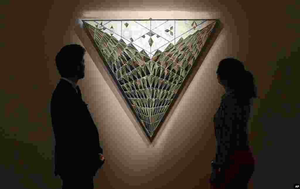 Visitors look at the 'Triangle of Hope' by Monir Farmanfarmaian as part of the Middle Eastern Art auction at the auction house Sotheby's in London, Friday, April 21, 2017. (AP Photo/Frank Augstein)