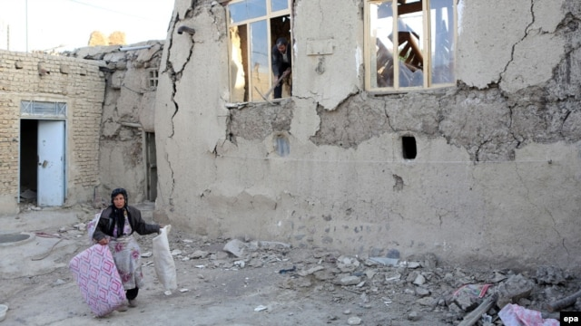 A woman carries a few belongings as she walks next to a severely damaged house in the city of Varzeqan, in the northwestern province of East Azerbaijan, on August 13.