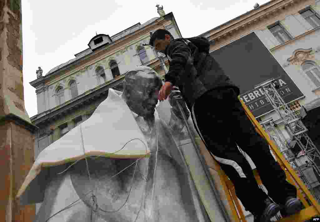 A worker unwraps a statue of late Pope John Paul II in front of The Cathedral of The Heart Of Jesus Christ in Sarajevo. (AFP/Elvis Barukcic)