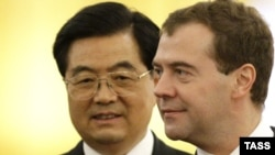 Chinese President Hu Jintao (left, with Russian President Dmitry Medvedev, abruptly changed plans amid scenes of prowling groups of armed men in Xinjiang.