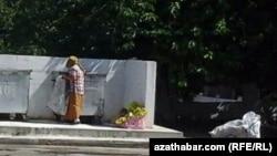 A woman picks through garbage cans in Ashgabat.