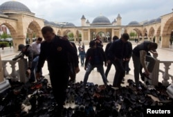 """Мусульмане снимают свою обувь перед мечетью """"Сердце Чечни"""". Грозный."""
